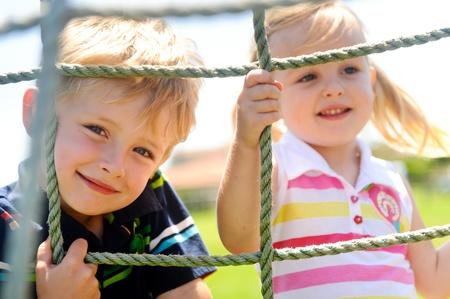 playground children: Dos ni�os peque�os, subiendo a la red en el patio de recreo Foto de archivo