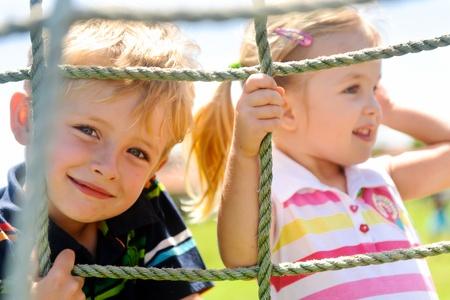 Twee jonge kinderen klimmen het net in de speel tuin