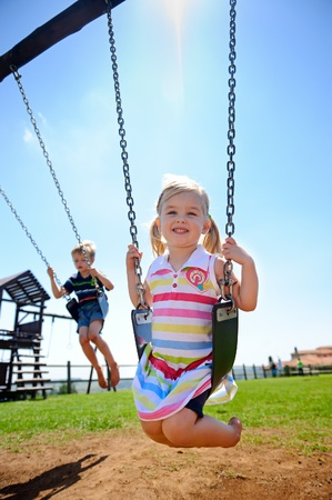 children playground: Young child on swing in playground outdoors