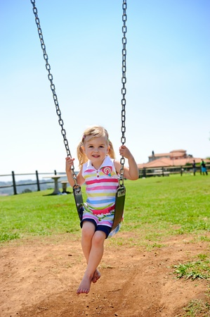 Young child on swing in playground outdoors Stock Photo - 8726723