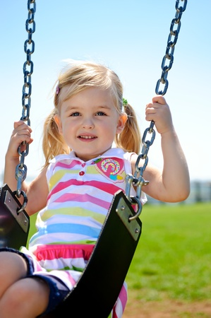 Young child on swing in playground outdoors photo