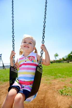 Young child on swing in playground outdoors Stock Photo - 8726947