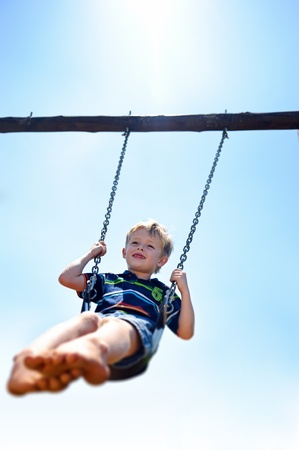 Young child plays on swing in the outdoor playground Stock Photo - 8726942