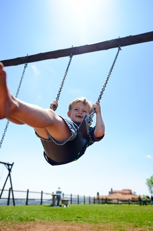 Young child plays on swing in the outdoor playground  photo