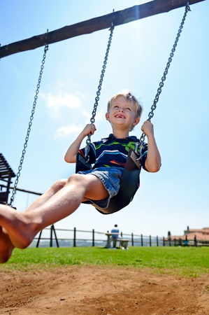 freedom leisure activity: Young child plays on swing in the outdoor playground