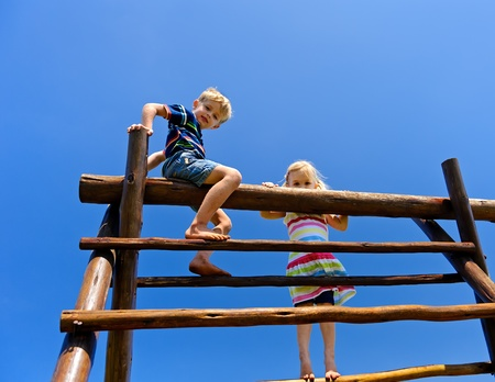 Two young children sitting at the top of playground equipment photo