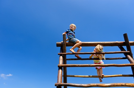 children playground: Two young children sitting at the top of playground equipment Stock Photo