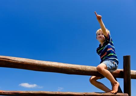 Bambino siede sulla cima di attrezzature del parco giochi