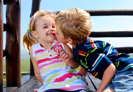 Young boy gives his sister a kiss on the cheek Stock Photo - 8726733