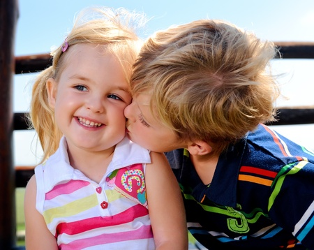 Young boy gives his sister a kiss on the cheek photo