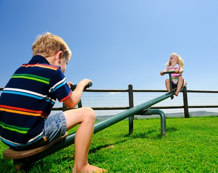 Kids playing at the see-saw in the playground Stock Photo - 8726552