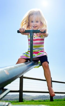 Young child playing with the seesaw at the playground photo