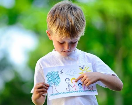 Niño lindo sostiene el dibujo de una familia