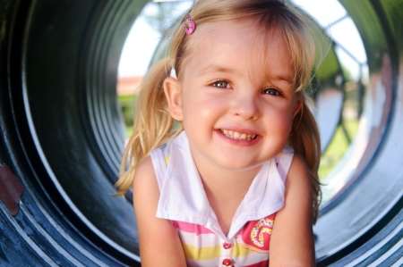 toddler girl: Cute girl poses in tunnel at the playground