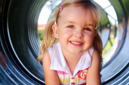 nourrisson: Jolie fille pose en tunnel au terrain de jeu Banque d'images