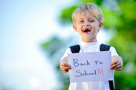 back posing: Young boy holds up handwritten sign Back to school!
