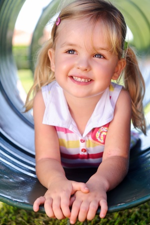 Cute girl poses in tunnel at the playground photo