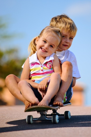 brother: Two young children sitting and playing with skateboard  Stock Photo