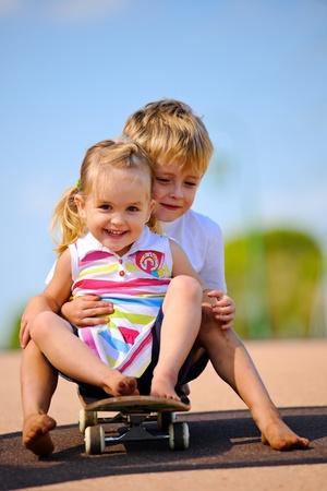 Dos niños sentados y jugando con la patineta  Foto de archivo - 8726919