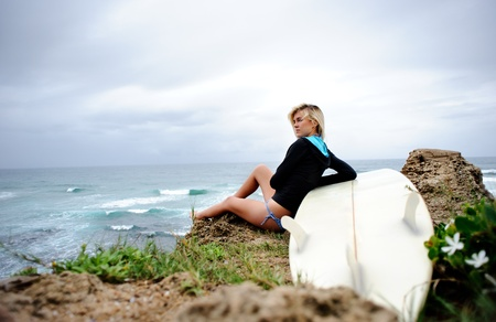 Female surfer sitting on cliffside with surfboard photo