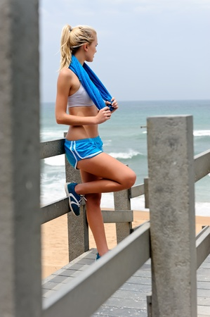 banister: Young blond female rests along the pathway Stock Photo