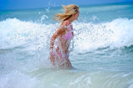 blonde bikini: Blonde bikini girl crashing into waves at the beach