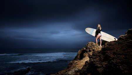 Young surfer holds her surfboard on cliff during stormy weather photo