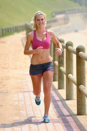 mujeres corriendo: Fit joven footing en un camino Foto de archivo