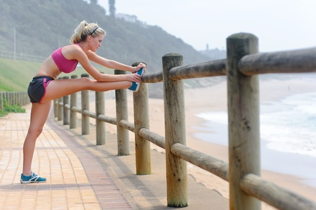 along: Young woman stretches along the pathway
