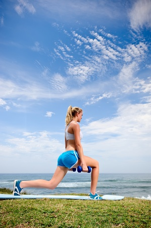 warms: Blond female warms up with dumbells