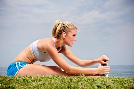estiramientos: Joven hembra rubia extiende su pierna en la hierba Foto de archivo