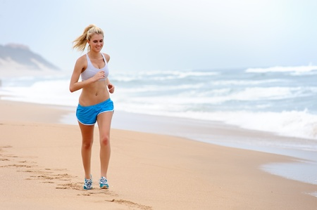 Young blond female runs along the beach  photo