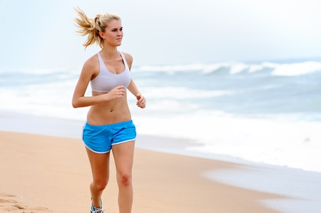 Young blond female runs along the beach