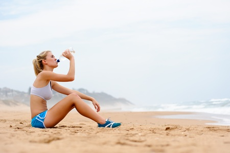 Young blond female in sports attire rests on sand Stock Photo - 8726944