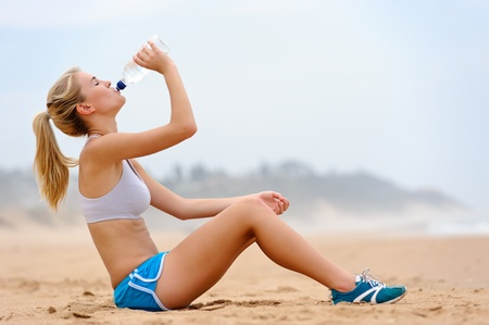Young blond female in sports attire rests on sand Stock Photo - 8726874
