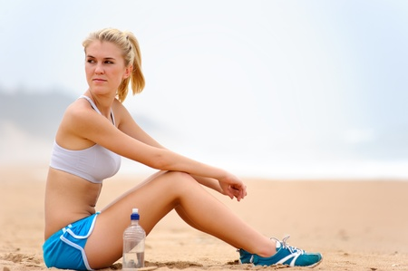 Young blond female in sports attire rests on sand photo