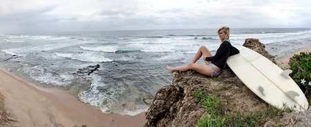 Young blonde surfer girl surveys they ocean and looks for waves. Panoramic image, large copyspace - XXL size photo