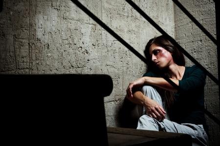 violencia intrafamiliar: Abusado de la mujer en la esquina de una escalera reconfortante a s� misma  Foto de archivo