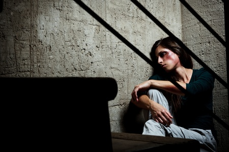 Abused woman in the corner of a stairway comforting herself Stock Photo - 8726439