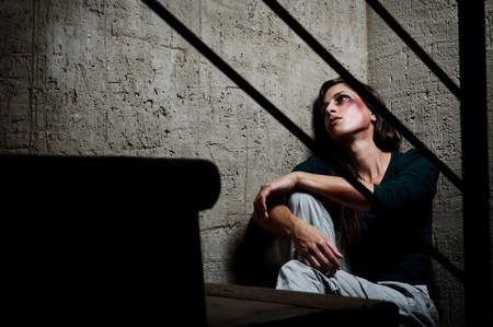 Abused woman in the corner of a stairway comforting herself Stock Photo - 8726432