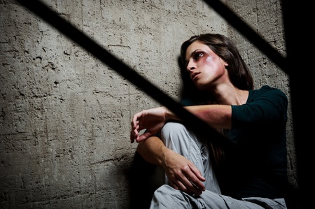 Abused woman in the corner of a stairway comforting herself  Stock Photo - 8726369