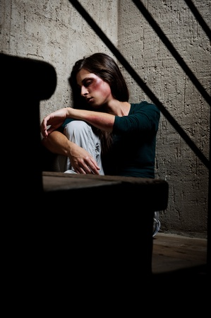 battered woman: Abused woman in the corner of a stairway comforting herself  Stock Photo