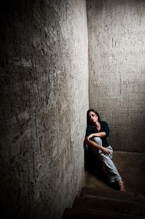 persona deprimida: Abusado de la mujer en la esquina de una escalera reconfortante a s� misma  Foto de archivo