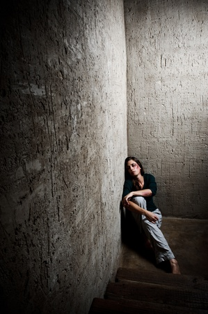horrors: Abused woman in the corner of a stairway comforting herself  Stock Photo