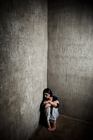 beaten woman: Abused woman in the corner of a stairway comforting herself  Stock Photo