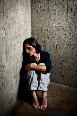 Abused woman in the corner of a stairway comforting herself after getting hit by her husband photo