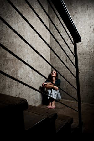 Abused woman in the corner of a stairway comforting herself Stock Photo - 8726386