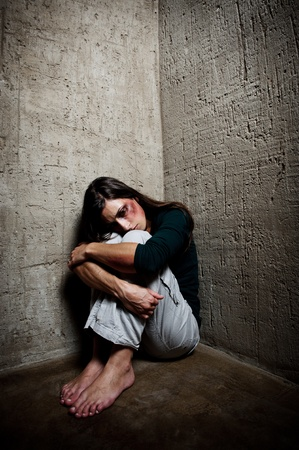 Abused woman in the corner of a stairway comforting herself  photo