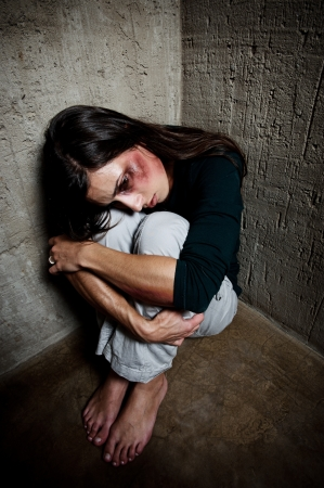 Abused woman in the corner of a stairway comforting herself  Stock Photo