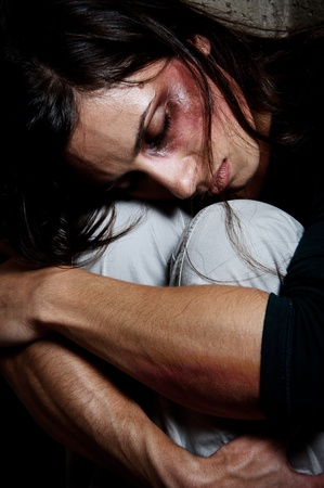 close up of an abused woman comforting herself